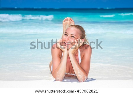 Beautiful woman on the beach, lying down and tanning on a white sandy seashore, enjoying summer vacation on a tropical beach resort - stock photo