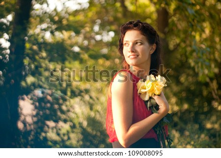 Beautiful woman on the nature, with roses in his hands - stock photo