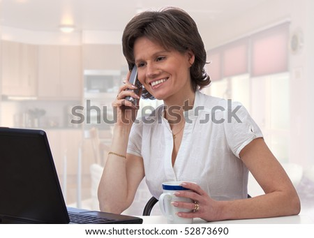 Beautiful woman on the phone in the kitchen while working on laptop and having coffee - stock photo