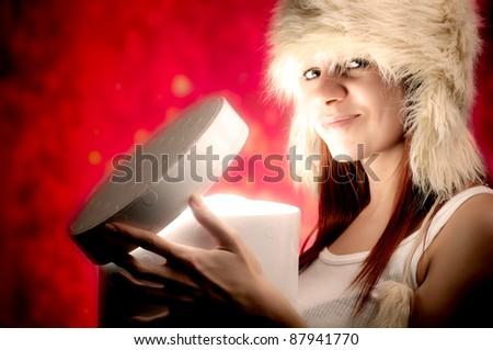 Beautiful woman opening a Christmas present.  Beautiful christmas woman series - stock photo