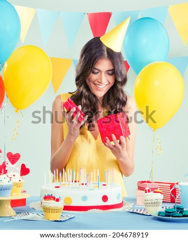 Beautiful woman opening a present at her birthday party - stock photo