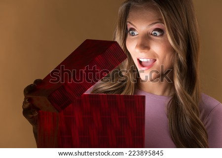 beautiful woman opening present box on brown background. surprised looking girl with emotions on face holding red box - stock photo