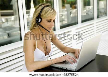 Beautiful woman outdoor with laptop and headset - stock photo