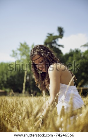 Beautiful woman outdoors on a golden wheat field. She stands meditating, wearing a white dress and feeling the sun of a hot summer afternoon. Color Image.