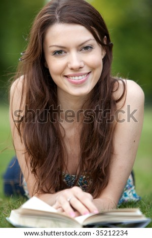 BEautiful woman outdoors reading a book and smiling - stock photo