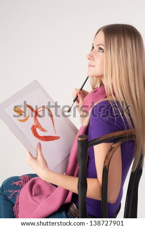 Beautiful woman painting something with paintbrush, sitting on chair - stock photo