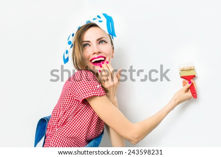 Beautiful woman painting the wall on light grey background - stock photo