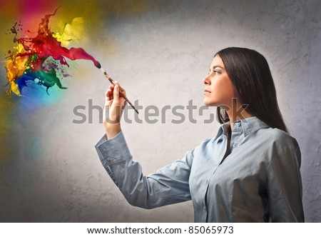 Beautiful woman painting with a paintbrush - stock photo