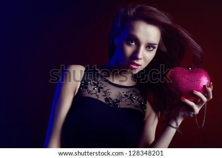 Beautiful woman partying wearing black dress and heart shaped purse