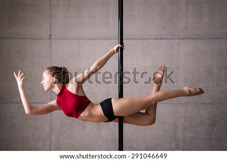 Beautiful woman performing pole dance. Shot with industrial concrete background.