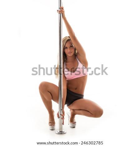 Beautiful woman performing pole dance. Studio shot on white background. - stock photo