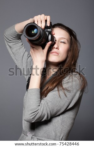 Beautiful woman photographer with camera at hands - stock photo