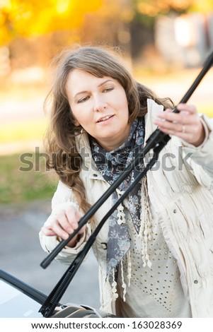 Beautiful woman picking up windscreen wiper and checking it - stock photo