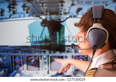 Beautiful woman pilot wearing uniform with epauletes and headset sitting inside airliner and pointing at cockpit during flight. - stock photo