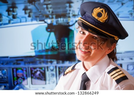 Beautiful woman pilot wearing uniform with epauletes, hat with golden wings sitting inside airliner with visible cockpit during flight. - stock photo