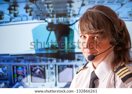 Beautiful woman pilot wearing uniform with epauletes, headset sitting inside airliner with visible cockpit during flight. - stock photo