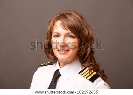 Beautiful woman pilot wearing uniform with epauletes looking ahead - stock photo
