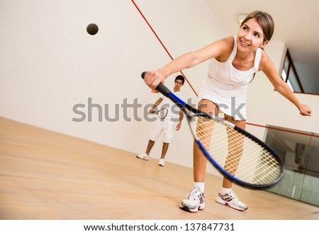 Beautiful woman playing a match of squash - stock photo