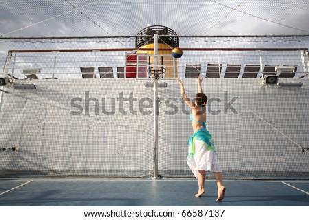beautiful woman playing basketball on deck of cruise ship. - stock photo