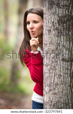 Beautiful woman playing hide and seek behind tree - stock photo