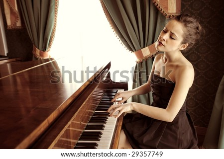 beautiful woman playing piano in a luxury interior - stock photo