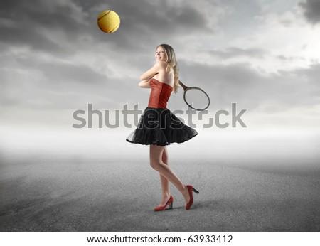 Beautiful woman playing tennis - stock photo
