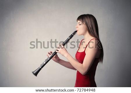 Beautiful woman playing the clarinet - stock photo