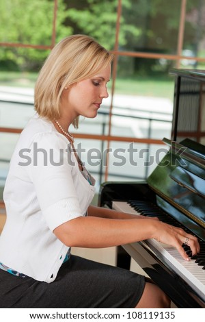 Beautiful woman playing the piano - stock photo