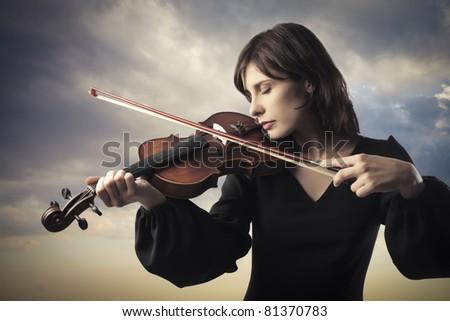 Beautiful woman playing the violin - stock photo