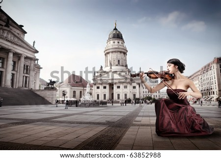 Beautiful woman playing the violin on a square in Berlin - stock photo
