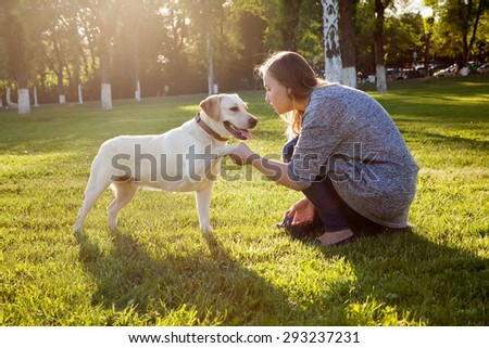 Beautiful woman playing with her dog Labrador retriever. - stock photo