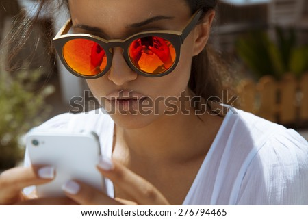 beautiful woman playing with her smart phone. horizontal outdoors shot. - stock photo