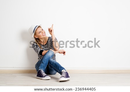 Beautiful woman pointing at copy space on empty wall in new house. Young smiling casual girl sitting on wooden floor and showing smth with her finger.  - stock photo