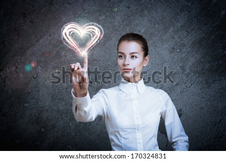 Beautiful Woman Pointing at Glowing Heart. Perfect Valentine's Day Concept.