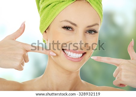 Beautiful woman pointing to her teeth.