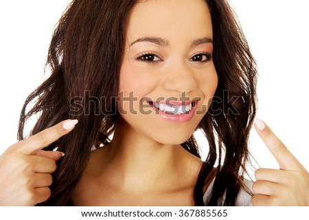 Beautiful woman pointing to teeth.