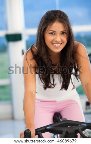 Beautiful woman portrait at the gym cycling - stock photo