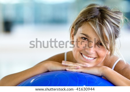 beautiful woman portrait at the gym smiling leaning on a pilates ball - stock photo