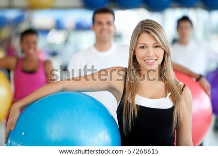 beautiful woman portrait at the gym smiling with a pilates ball