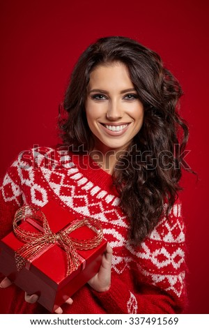 Beautiful woman portrait hold gift in christmas color style . Smiling happy girl on red background. - stock photo