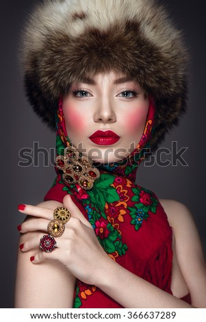 Beautiful woman portrait in russian style with fur hat and scarf - stock photo