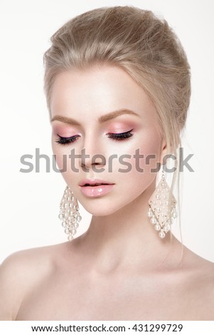 Beautiful woman portrait in tender colors. Young lady posing in studio with closed eyes and earrings in ears. Pure skin, nice make up. - stock photo