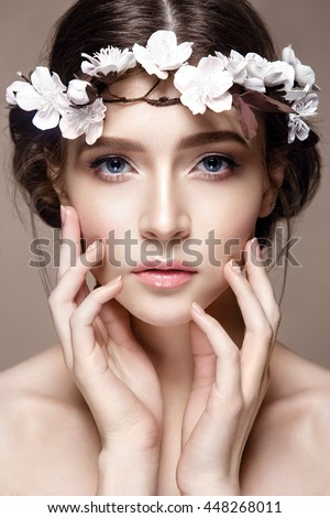 Beautiful woman portrait in tender colors. Young lady posing in studio with flowers on head. Pure skin, nice make up. - stock photo