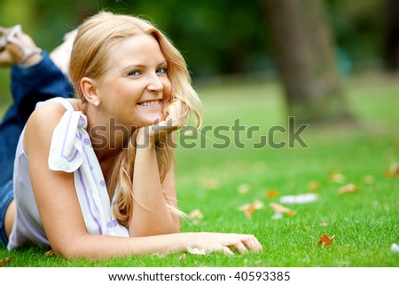 Beautiful woman portrait lying outdoors and smiling - stock photo
