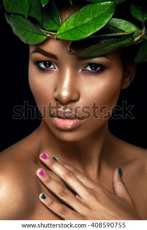 Beautiful woman portrait on black background. Young afro girl posing with green leaves. Gorgeous make up. Pure skin - stock photo