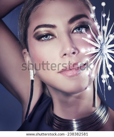 Beautiful woman portrait on dark gorgeous female with stylish shiny makeup wearing fashionable accessories and holding decorative bright snowflake - stock photo