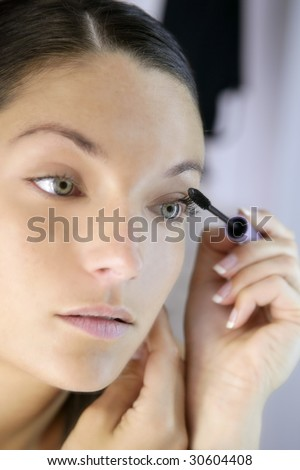 Beautiful woman portrait on the mirror with eye self makeup