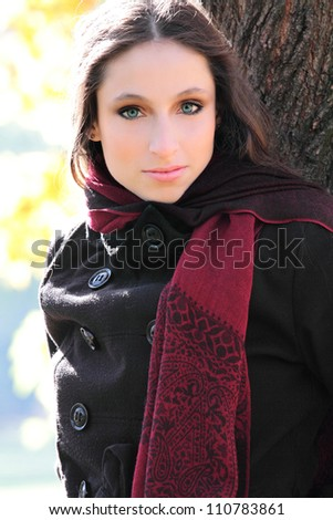 Beautiful woman portrait outdoors leaning on a tree