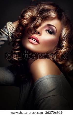 Beautiful Woman Portrait. Sexy Girl. Beauty model posing over dark background. Fashion Beauty Portrait. Holiday Makeup