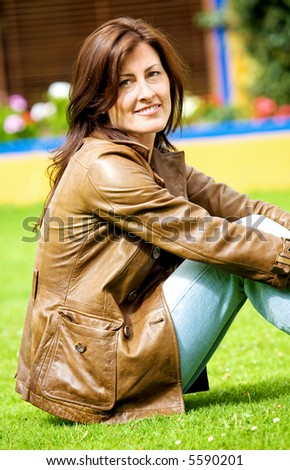 beautiful woman portrait smiling outside her home sitting on the grass - stock photo
